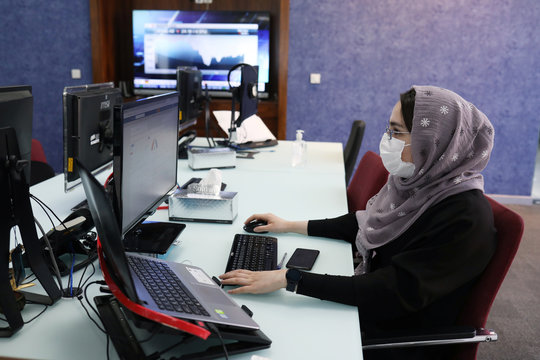 An employee of a stock brokerage firm wearing a protective face mask monitors the stock prices on her computer, following the outbreak of the coronavirus disease (COVID-19), at the brokerage house in Tehran