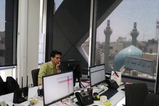 An employee of a stock brokerage firm monitors the stock prices on his computer, following the outbreak of the coronavirus disease (COVID-19), in Tehran