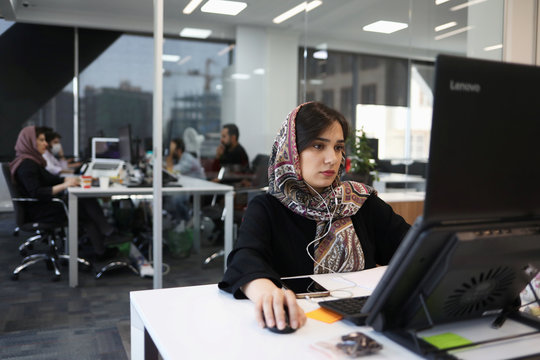 An employee of a stock brokerage firm monitors the stock prices on her computer, following the outbreak of the coronavirus disease (COVID-19), at the brokerage house in Tehran