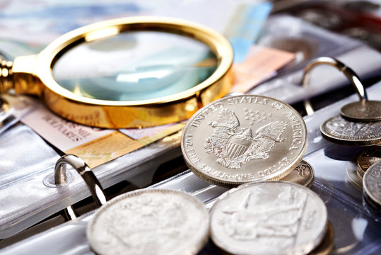 Silver dollar and numismatic coins with magnifying glass