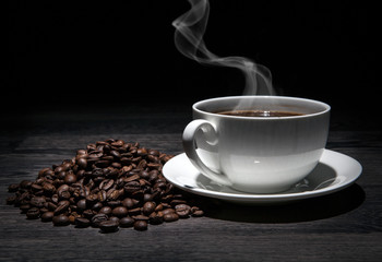 Wall Mural - cup of hot coffee and roasted coffee beans on a wooden table on a black background