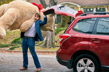 Man grabs a valentines day gift out of the trunk of his car, surprising his partner with a large teddy bear.