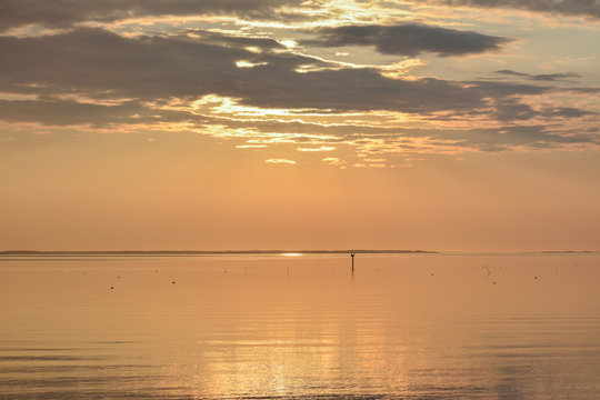 Sunrise over the Chesapeake Bay with crab pot buoys visible on the calm water surface.