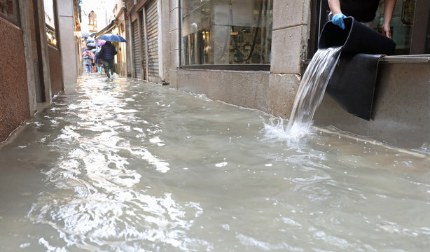 person emptying the interior of the shop flooded after the flood