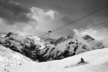 Wall Mural - Chair-lift, snowy ski track prepared by snowcat, skiers and snowboarders in ski resort