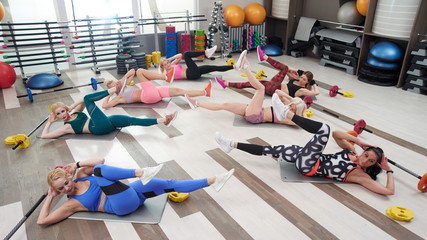 Fitness workout in the gym. Group of women doing exercises for abdominal muscles in colorful sportswear