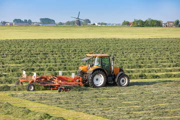 A tractor with a mower in Sassenheim. On the background the historic Lisserpoel windmill. On the Rooversbroekdijk in the Hellegatspolder in the Netherlands.