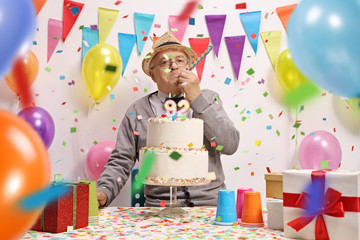 Elderly man celebrating birthday with a cake, balloons and confetti