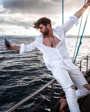 Handsome young man holding perfume bottle, while sitting on the rail of a yacht.
