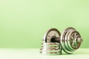 Large metal heavy dumbbell with pancakes on a green background. Fitness or bodybuilding concept background.