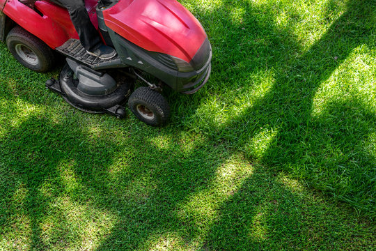 Top down above view of professional lawn mower worker cutting fresh green grass with landcaping tractor equipment machine. Garden and backyard landscape lawnmower service and maintenance