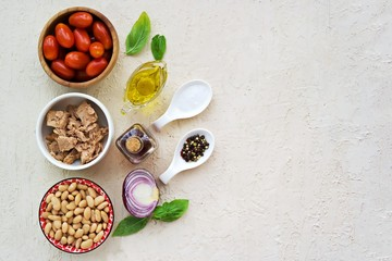 Prepared salad ingredients with canned tuna, white beans and tomato on a light concrete background. Italian food. Salad recipes. Copyspace, top view.