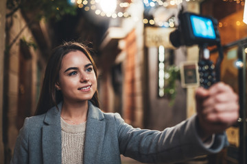Fotomurales - Female blogger shooting video for vlog social media with digital camera. Smiling woman vlogger taking photo selfie on background light night city illuminations