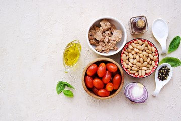 Prepared salad ingredients with canned tuna, white beans and tomato on a light concrete background. Italian food. Salad recipes. Copyspace, top view