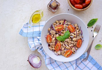 Traditional Italian salad with boiled beans, tomatoes, canned tuna and purple onions in a gray plate on a light concrete background. Dressed with olive oil. Italian food.