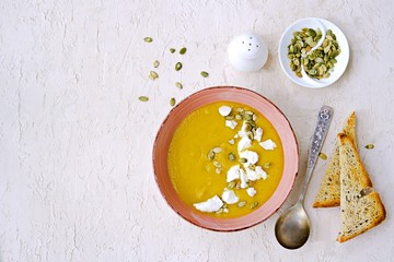 Pumpkin puree soup in a pink clay bowl on a light concrete background. Served with feta cheese, pumpkin seeds and croutons of white bread. Thanksgiving concept. Copyspace.