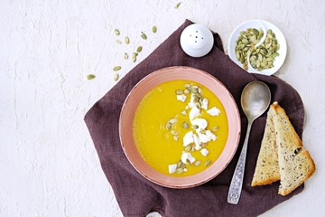 Pumpkin puree soup in a pink clay bowl on a light concrete background. Served with feta cheese, pumpkin seeds and croutons of white bread. Thanksgiving concept.