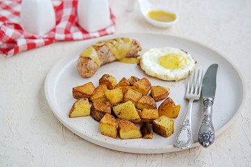 Large breakfast, home fries potatoes, pork sausage and fried egg on a white clay plate on a light concrete background. American food
