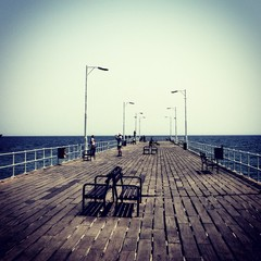 People On Wooden Pier Over Sea Against Clear Sky