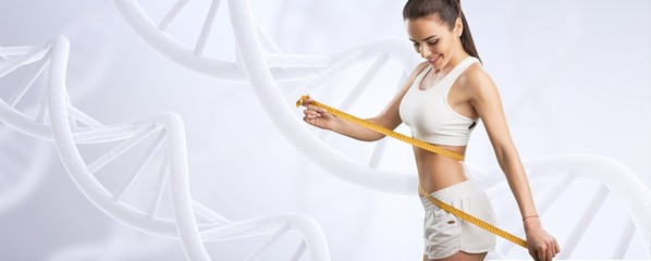 Beautiful fitness girl measuring her waistline with measure tape