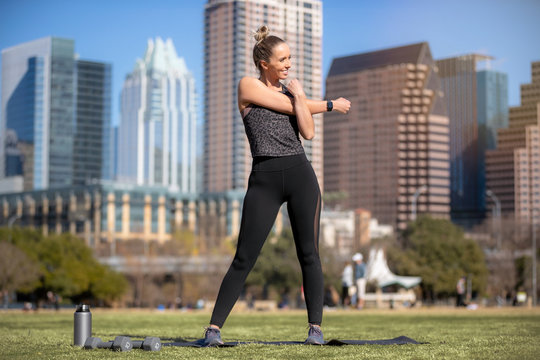 Toned, lean, fit, muscular, female athlete stretching and warming up before fitness exercise routine outdoors on grass lawn in city park