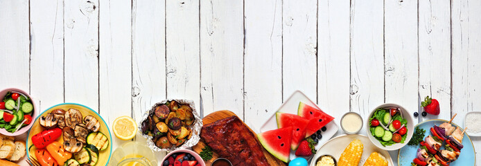 Summer BBQ or picnic food long border. Various grilled meats, vegetables, fruits, salad and potatoes. Top view over a white wood banner background. Copy space.