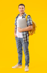 Male student with laptop on color background