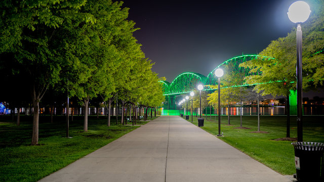 Walkway at Waterfront Park in Louisville, KY with the Big Four bridge in background lit green to mark those who have lost their lives to COVID-19.