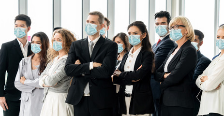Confident business people with face mask protect from Coronavirus or COVID-19. Concept of help,...