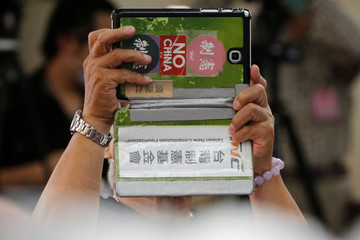"""A man with a """"No China"""" sticker on his phone is seen at a press conference about Taiwan's efforts to get into the World Health Organization in Taipei,"""