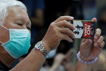 """A man with a """"No China"""" sticker on his phone is seen at a press conference about Taiwan's efforts to get into the World Health Organization"""