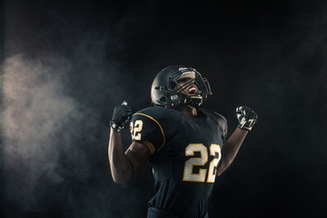 African American football player isolated on black.