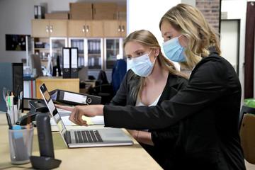 Zwei Büroangestellte mit Mund- und Nasenschutz arbeiten gemeinsam am Schreibtisch