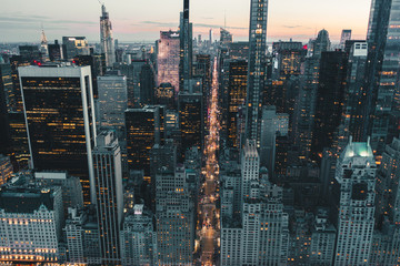 Fototapeten New York Dramatic View of Dark Epic Manhattan, New York City Avenue right after Sunset with City Lights