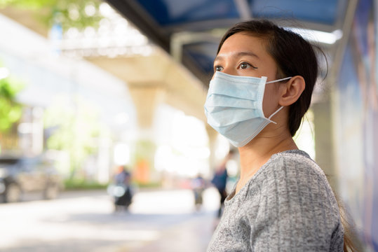 Face of young Asian woman with mask thinking while sitting at the bus stop