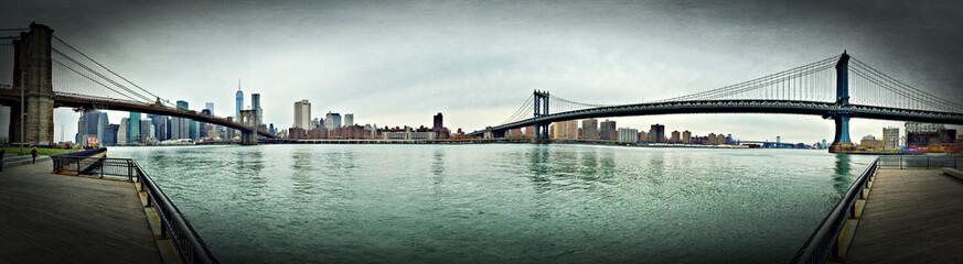 Panoramic View Of Brooklyn Bridge And Manhattan Bridge Over East River Against Sky