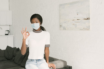 african american girl in medical mask showing okay gesture while looking at camera