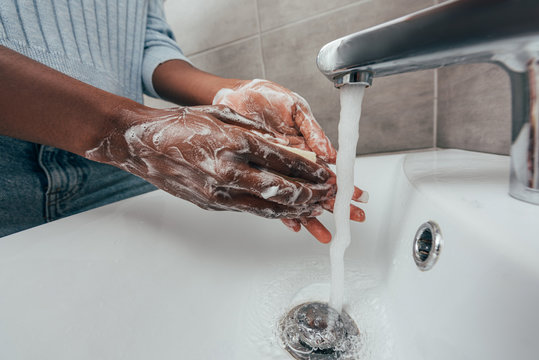cropped view of african american woman washing hands with soap