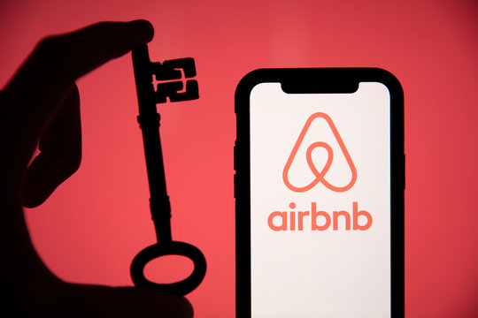 LONDON, UK - May 15 2020: Airbnb home rental logo on a phone with a key