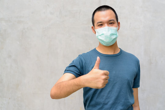 Young Asian man giving thumbs up with mask for protection from corona virus outbreak outdoors