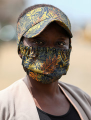 A woman poses for a picture with a fabric face mask on, matching with her hat, following the spread of the coronavirus disease (COVID-19) in Lagos
