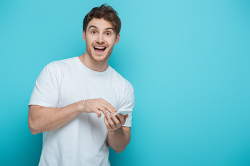 Keuken foto achterwand Honden excited guy looking at camera while chatting on smartphone on blue background