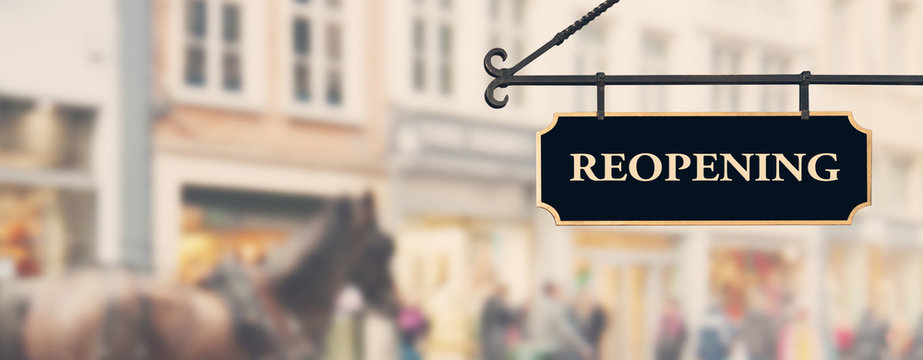 Reopening economy concept. Sign with word reopening hanging against open shop windows background. Restarting business after end of coronavirus lockdown. Economy recovery symbol