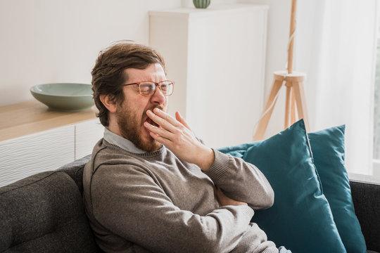 Bored man yawn sitting on the sofa