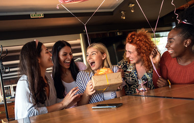 Group of girls surprise their girlfriend with a birthday party at restaurant.