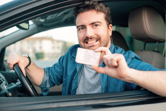 Cheerful man holding driver license in his car