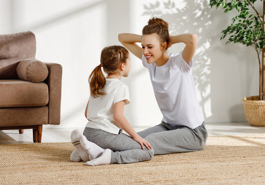 Fit mother and daughter training together at home.