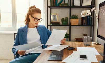 Happy young woman working with documents and computer at home
