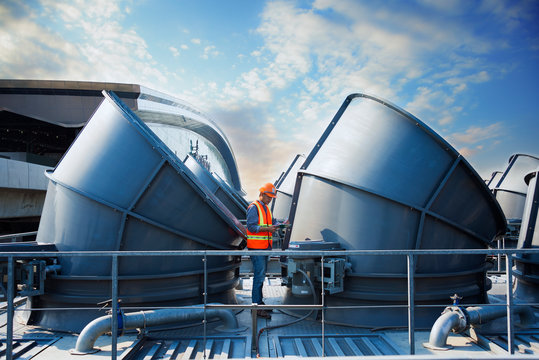 worker standing  top of cooling tower on blue sky background