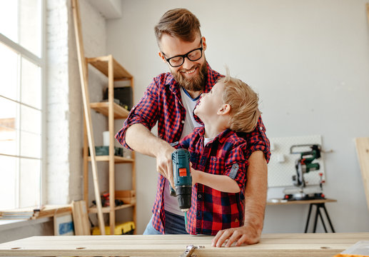 Happy kid helping father in carpentry studio.